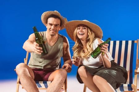 Young couple with beer bottles sitting in deck chairs on blue background