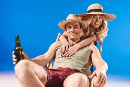 Woman hugging man sitting in deck chair with beer isolated on blue