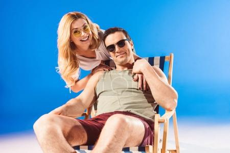 Woman hugging man relaxing in deck chair on blue background