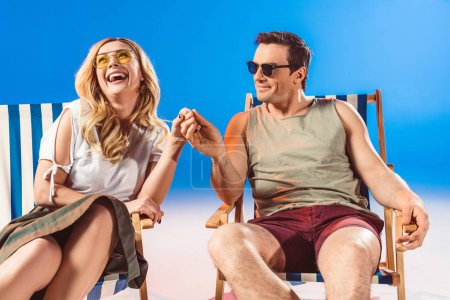 Young couple resting in beach chairs and holding hands on blue background