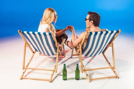 Young attractive couple holding hands in deck chairs by beer bottles on blue background