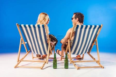 Smiling young couple relaxing in deck chairs by beer bottles on blue background