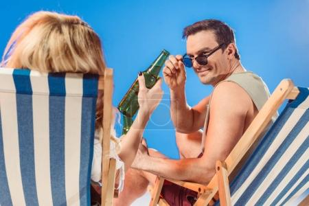 Man in sunglasses looking at beer bottle in female hand while sitting in beach chair isolated on blue