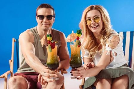 Young smiling couple with cocktails resting in deck chairs on blue background