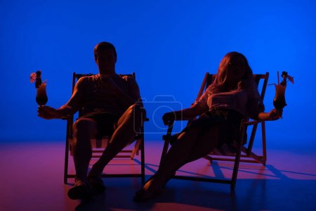 Silhouettes of man and woman holding glasses with cocktails resting in deck chairs on blue background in dark light