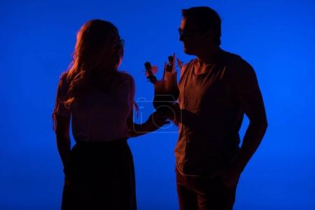 Beautiful couple silhouettes clinking with cocktails isolated on blue in dark light