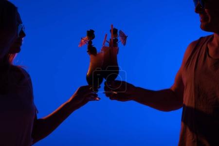 Man and woman toasting with cocktails isolated on blue in dark light