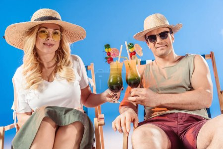 Young attractive couple toasting with cocktails resting in deck chairs on blue background
