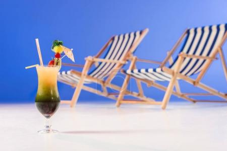 Cocktail in glass by deck chairs on blue background