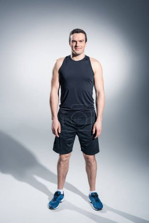 Confident sportive man in black clothes and sneakers on grey background