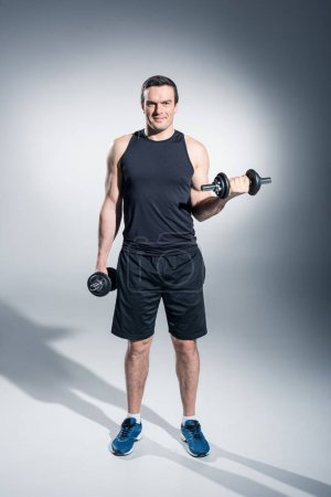 Young man athlete lifting dumbbells on grey background