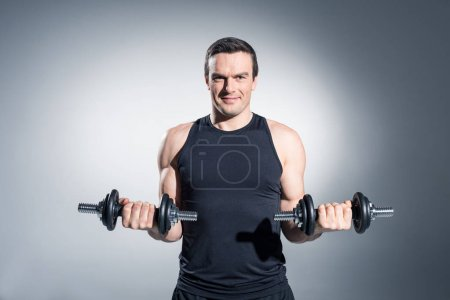 Photo for Active man lifting dumbbells on grey background - Royalty Free Image