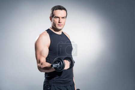 Sportsman working out with heavy dumbbells on grey background