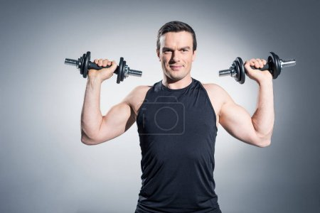 Photo for Confident sportive man exercising with dumbbells on grey background - Royalty Free Image