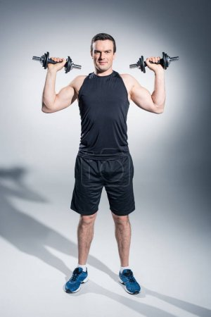 Photo for Attractive man athlete lifting dumbbells on grey background - Royalty Free Image