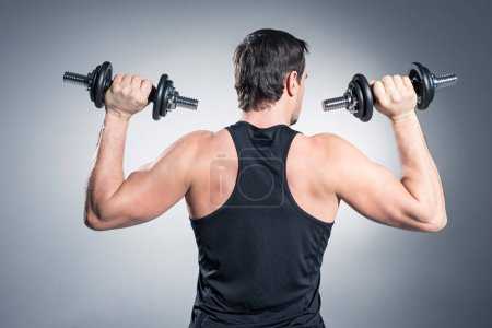 Rear view of man exercising with dumbbells on grey background
