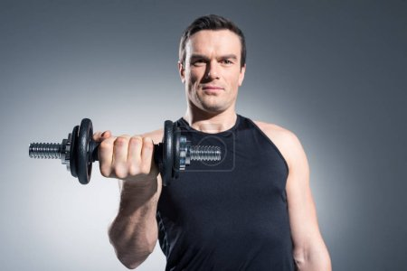 Young man athlete exercising with dumbbell on grey background