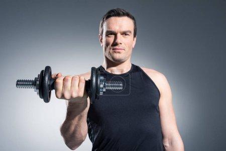Photo pour Jeune homme sportif exerçant avec haltère sur fond gris - image libre de droit