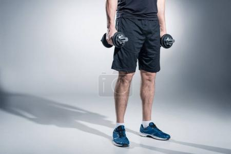 Close-up view of sportsman working out with heavy dumbbells on grey background