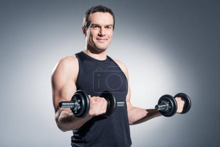 Smiling man lifting dumbbells on grey background