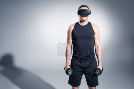 Photo for Young man athlete lifting dumbbells while wearing vr glasses on grey background - Royalty Free Image