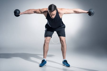 Attractive man athlete lifting dumbbells on grey background