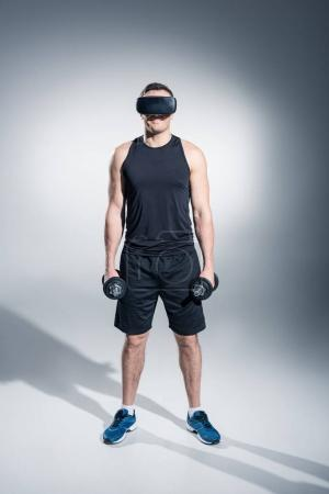 Photo for Sportive man exercising with dumbbells while wearing vr glasses on grey background - Royalty Free Image