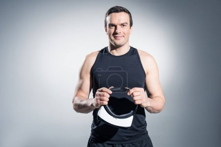 Smiling man holding vr glasses on grey background