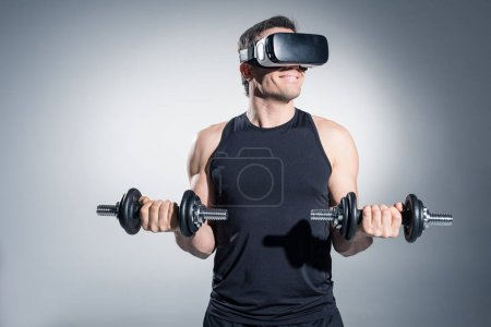 Photo for Active man training with dumbbells while wearing vr glasses on grey background - Royalty Free Image