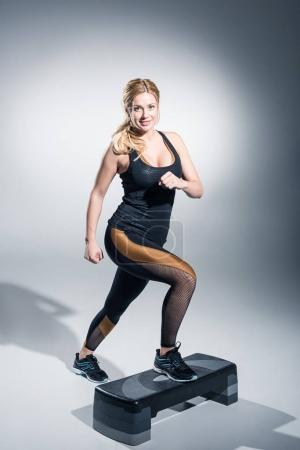 Blonde woman working out on step platform on grey background