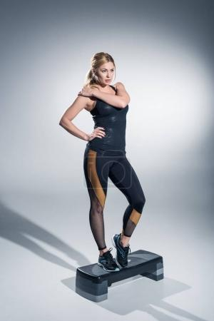 Blonde sportswoman training on step platform on grey background