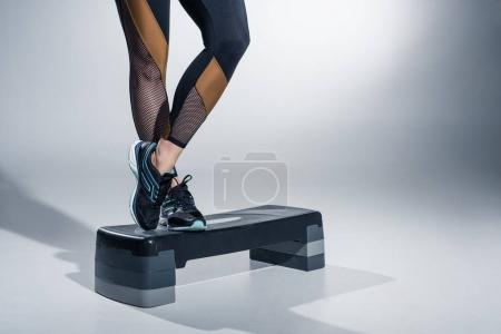 Photo for Close-up view of woman standing on step platform on grey background - Royalty Free Image
