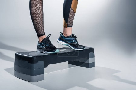 Close-up view of woman training on step platform on grey background