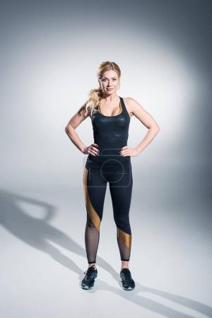 Attractive sportive woman in black clothes and sneakers on grey background