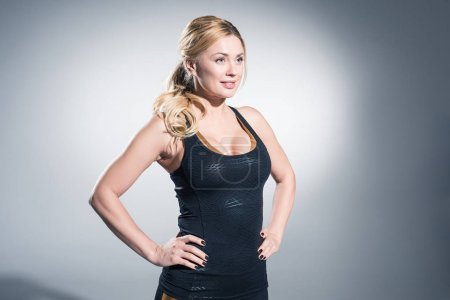 Confident blonde woman in sports clothes on grey background