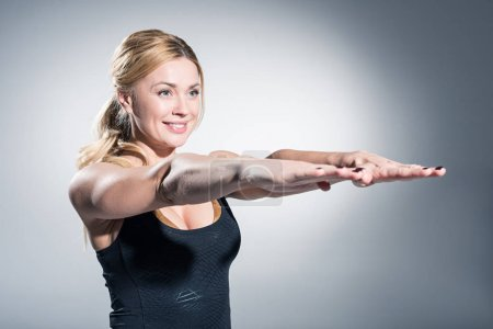Photo for Attractive sportive woman with outstretched hands on grey background - Royalty Free Image