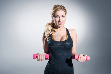Confident blonde woman training with dumbbells on grey background