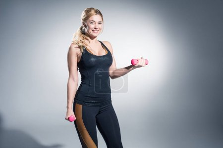 Attractive sportive woman working out with dumbbells on grey background