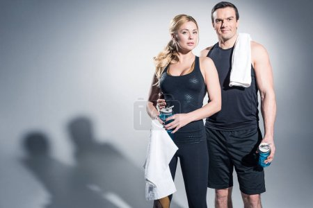 Sportive couple standing with towels and water bottles on grey background