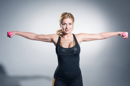 Blonde woman weightlifting with dumbbells on grey background