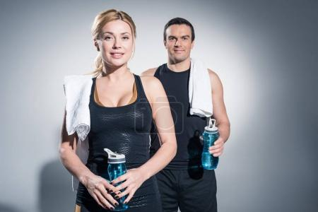 Couple of sportive people man and woman standing with towels and water bottles on grey background