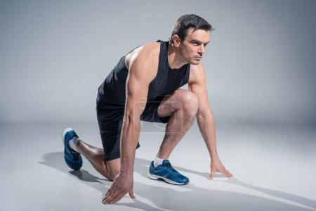 Young athletic man on low position ready for run on grey background