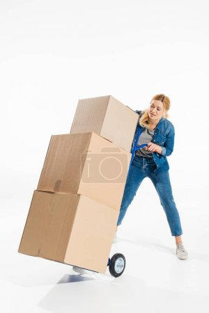 Attractive woman struggling with delivery cart loaded with boxes isolated on white