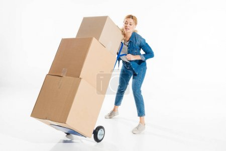 Young woman holding trolley cart loaded with boxes isolated on white