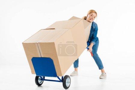 Photo pour Belle femme essayant de pousser le chariot de livraison avec des boîtes isolées sur blanc - image libre de droit