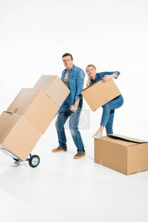 Photo for Young couple moving cardboard boxes with trolley cart isolated on white - Royalty Free Image