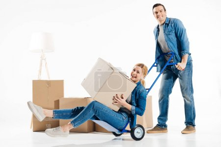 Man pushing trolley cart with woman holding box during flat moving isolated on white