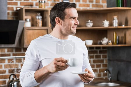 handsome man smiling and looking away while drinking coffee in kitchen