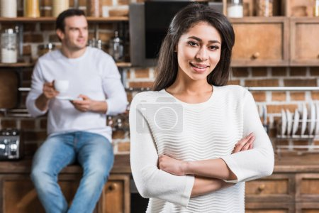 Photo for Beautiful young african american woman standing with crossed arms and smiling at camera while boyfriend drinking coffee behind in kitchen - Royalty Free Image