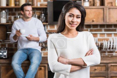 Foto de Hermosa joven Afro Americana de pie con los brazos cruzados y sonriendo a cámara mientras novio tomando café detrás en la cocina - Imagen libre de derechos